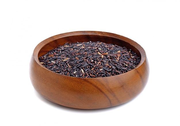 Riceberry ongepelde rijst in de houten kom die op witte oppervlakte wordt geïsoleerd