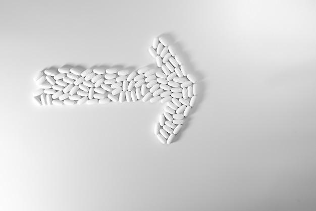 Richtingspijl met pillen wordt op witte achtergrond, geneeskundeconcept worden geïsoleerd gemaakt dat