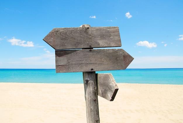 Richtingverkeersteken met houten pijlen op strand en overzeese achtergrond