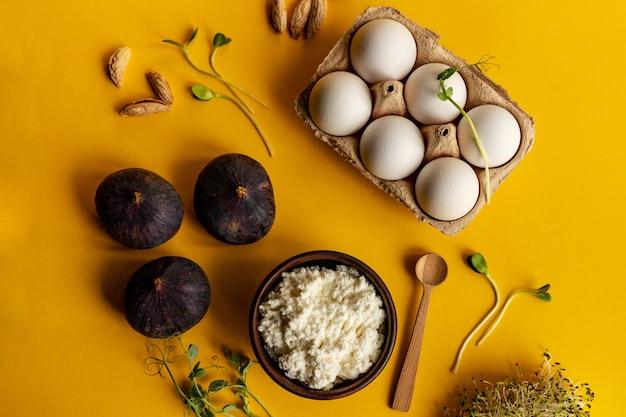 Ricotta kaas, 6 witte eieren, vijgen, micro groen en amandel op gele achtergrond