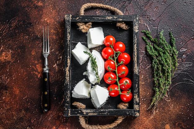 Ricotta roomkaas in een houten bakje met basilicum en tomaat