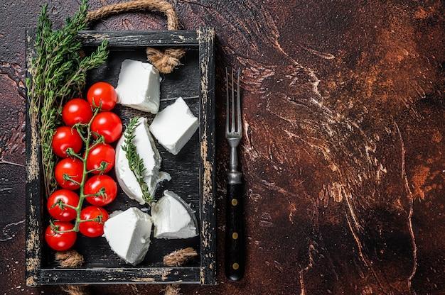 Ricotta roomkaas in een houten dienblad met basilicum en tomaat. donkere achtergrond. bovenaanzicht. ruimte kopiëren.