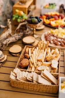 Rieten brood en ontbijtgranen dienblad met gesneden broodstokjes en koekjes op een houten vakantietafel