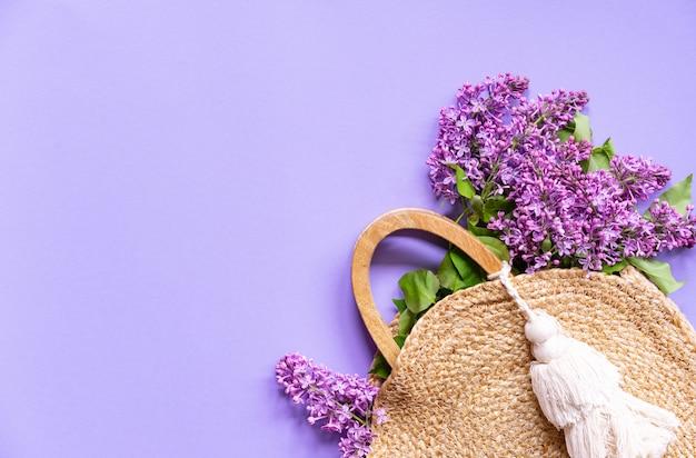 Rieten handtas met lila bloemen, lente tijd, zomer creatief concept, paarse achtergrond, kopie ruimte, bovenaanzicht