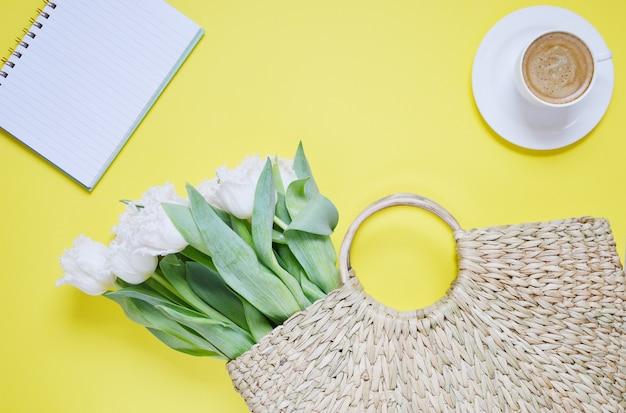 Rieten handtas met tulpenbloemen, koffiekopje en notitieboek