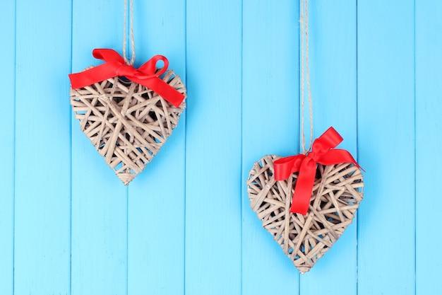 Rieten harten met rode strik op houten achtergrond