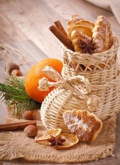 Rieten kerstsok gevuld met koekjes, kaneelstokjes, gekonfijte citroen en steranijs