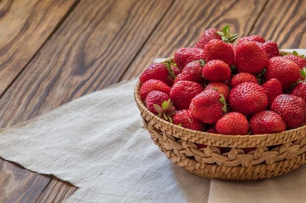 Rieten kom met smakelijke aardbeien op houten tafel, ruimte voor tekst