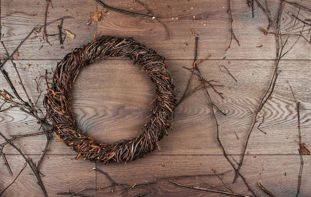 Rieten krans van berkentakken op een houten achtergrondexemplaarruimte. een krans van takken weven.