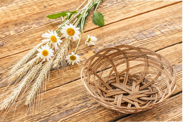 Rieten mand, boeket kamille bloemen en droge aartjes van tarwe op oude houten planken. bovenaanzicht.