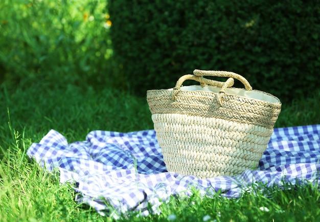 Rieten mand en plaid voor picknick op groen gras