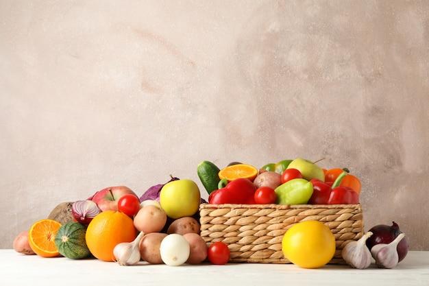 Rieten mand, groenten en fruit op witte houten ruimte voor tekst