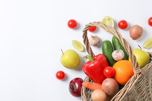 Rieten mand, groenten en fruit op witte ruimte voor tekst