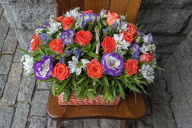 Rieten mand met bloemen op houten stoel die zich dichtbij granietmuur bevindt.