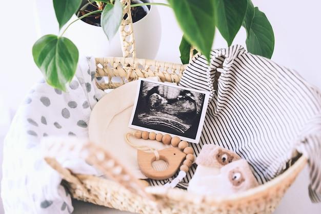 Rieten mand met echobeelden en spullen voor pasgeboren baby