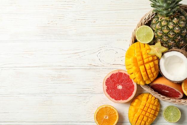 Rieten mand met exotische vruchten op witte houten achtergrond, bovenaanzicht en ruimte voor tekst