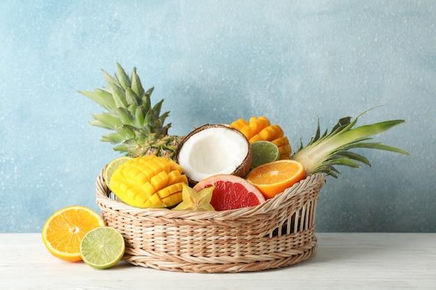 Rieten mand met exotische vruchten op witte houten achtergrond, ruimte voor tekst