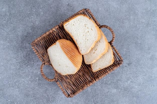 Rieten mand met gesneden wit brood op stenen tafel.