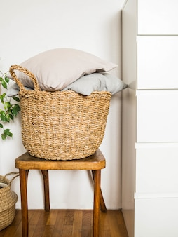 Rieten mand met grijze kussens op een houten uitstekende stoel tegen witte muur