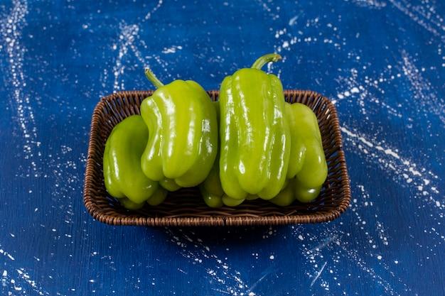 Rieten mand met groene paprika's op marmeren oppervlak.