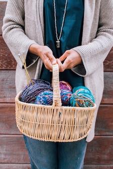 Rieten mand met kleurrijke heldere ballen van wolgaren voor breien in vrouwelijke handen.