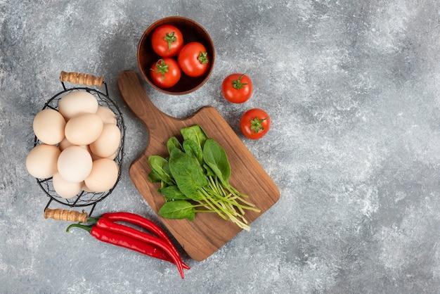 Rieten mand met rauwe biologische eieren en verse groenten op marmer.