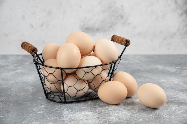 Rieten mand met rauwe biologische eieren op marmer.
