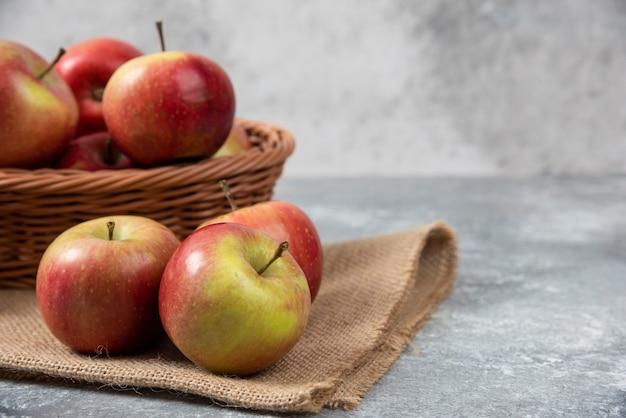 Rieten mand met rijpe glanzende appels op marmeren oppervlak.