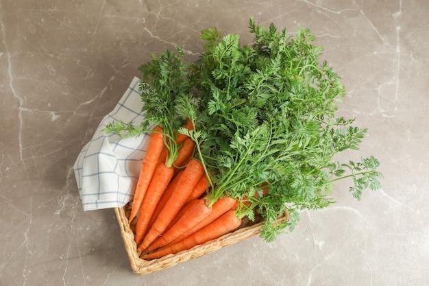 Rieten mand met rijpe wortelen op grijze tafel, ruimte voor tekst