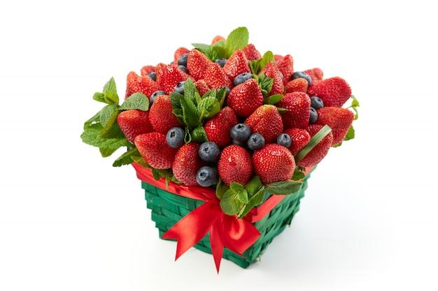 Rieten mand met sappige aardbeien, bosbessen versierd met verse muntblaadjes op een witte achtergrond