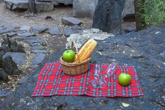 Rieten mand met stokbrood, wijn en appels voor picknick
