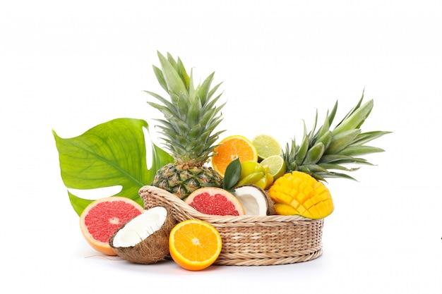 Rieten mand met verse exotische vruchten die op wit worden geïsoleerd