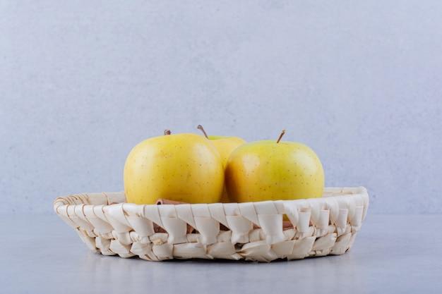 Rieten mand met verse gele appels op stenen tafel.