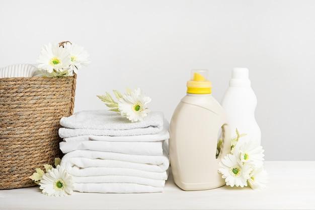 Rieten mand met wit linnen, wasgel en wasverzachter op een witte tafel met gerberabloemen. mockup lente wasdag.