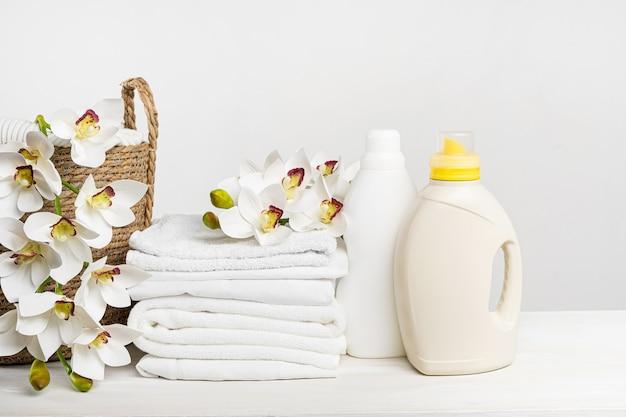 Rieten mand met wit linnen, wasgel en wasverzachter op een witte tafel met orchideebloemen. mockup wasdag in een tropisch hotel.