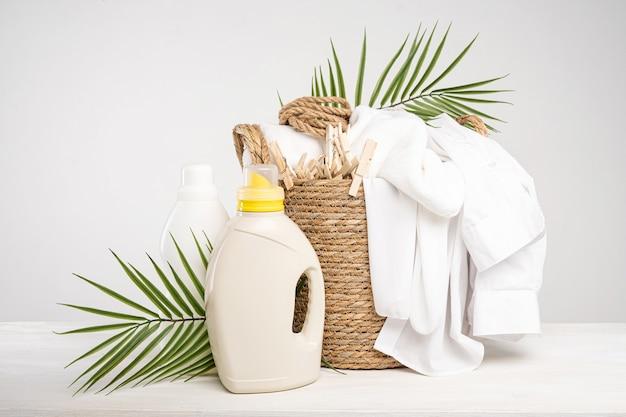 Rieten mand met wit linnen, wasknijpers, waslijn, wasgel en wasverzachter op een witte tafel met palmtakken. mockup wasdag in een tropisch hotel.