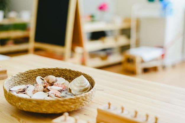 Rieten mand met zeeschelpen in een montessoriklasse