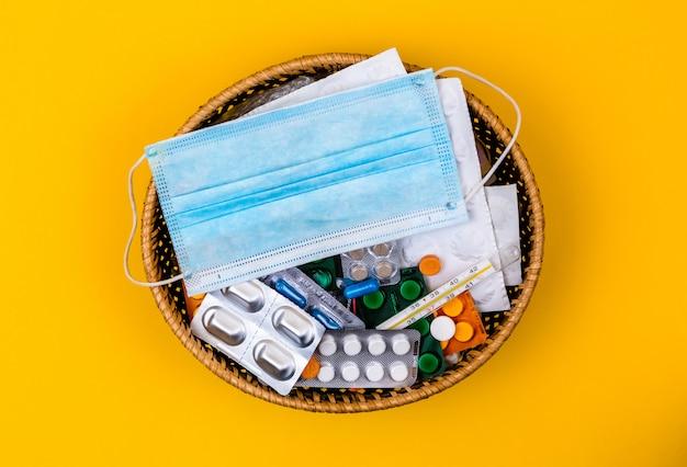 Rieten mand op de gele achtergrond. madical masker op de mand. kopieer ruimte. plaats voor tekst en design. bovenaanzicht. platte lay-outpillen en vitamines.