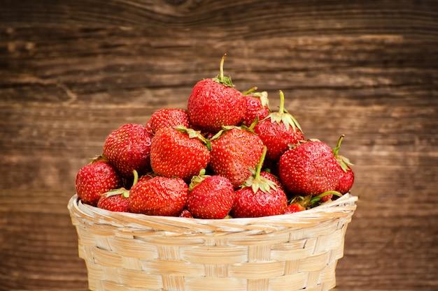 Rieten mand van rijpe aardbeien op bruine houten tafel.