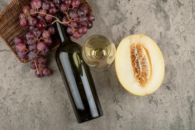 Rieten mand van rode druiven met glas witte wijn en gesneden meloen.