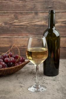 Rieten mand van rode druiven met glas witte wijn op marmeren tafel.