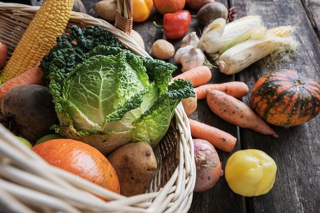 Rieten mand vol met verschillende kleurrijke groenten verstrooiing op rustieke houten planken.