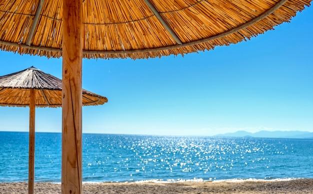 Rieten parasols en ligbedden op het lege strand