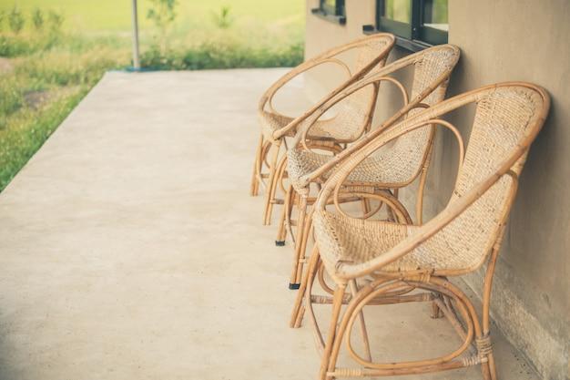 Rieten rotan stoel op balkonterras patio om uit te rusten in de buurt van de tuin