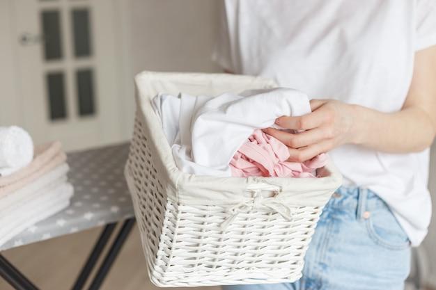 Rieten rustieke mand met gewassen kleren in de hand van de vrouw klaar om te strijken