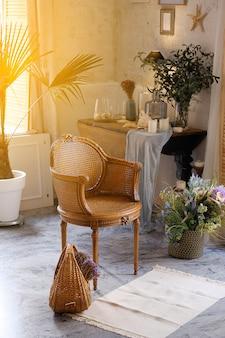 Rieten stoel en manden met bloemen in een kamer