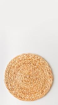 Rieten strotribune die op witte achtergrond wordt geïsoleerd. rechtopstaande foto als plat lag, bovenaanzicht minimale sjabloon voor sociale media