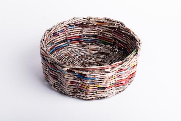 Rieten vaas gemaakt van oude kranten op een witte achtergrond. voorbeeld van hergebruik van papier