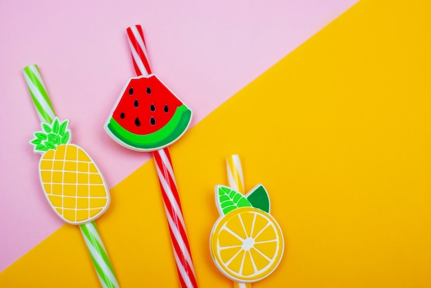 Rietjes in de vorm van watermeloen, citroen en ananas op een roze en gele achtergrond