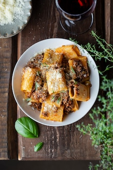 Rigatoni pasta met ragu bolognese saus, parmezaan en basilicum